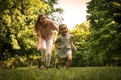 Mother and daughter running trough meadow. Mother chases her daughter. stock photos