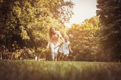 Mother and daughter running trough meadow. Mother chases her daughter. royalty free stock images