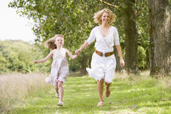 Mother and daughter running on woodland path. Hand in hand stock images