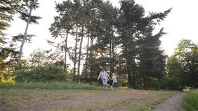 Mother and daughter running on woodland path. Beautiful garden, good mood stock video footage