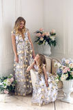 Mother and daughter are in the same floral dresses Royalty Free Stock Photos