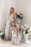 Mother and daughter are in the same floral dresses Stock Photos