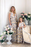 Mother and daughter are in the same floral dresses royalty free stock image