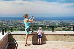 Mother with daughter at San Marino observation deck. Mom taking landscape photo with smartphone. Child looking at italian coast o stock photography