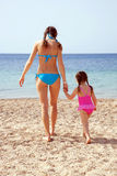 Mother and daughter on the sandy beach. Stock Photos