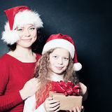 Mother and Daughter in Santa Hat holding Christmas Gift Stock Photos
