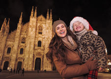 Mother and daughter in Santa Hat near Duomo in Milan, Italy. Family Christmas holidays in style. Portrait of happy mother and daughter in Santa Hat in the front Royalty Free Stock Photography