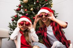 Mother and daughter in santa hats. Cheerful mother and daughter in santa hats having fun with shiny baubles at home Royalty Free Stock Photos