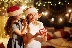 Mother and daughter in Santa hats give presents in a room on Ch royalty free stock photos