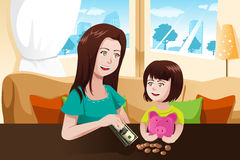 Mother and daughter saving money to a piggy bank Royalty Free Stock Images