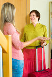 Mother and daughter saying goodbye in the room. Happy elderly mother and her daughter saying goodbye in the room near the door stock photography