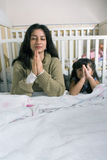 Mother and Daughter Saying Prayer-Vertical. Mother and daughter saying prayers at bedtime stock photo