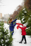 Mother with daughter of school age have built a snowman. Royalty Free Stock Photo