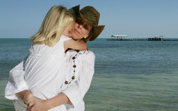 Mother and daughter at sea. A woman holding her young daughter in her arms, ocean in the background Stock Image