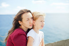 Mother and daughter on sea background Stock Photo