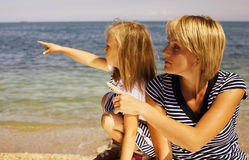 Mother with daughter at sea cost together. Happy family Royalty Free Stock Image