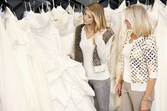 Mother and daughter selecting bridal gown in boutique Royalty Free Stock Images
