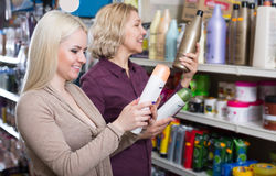 Mother and daughter selecting shampoo Royalty Free Stock Images