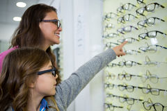 Mother and daughter selecting spectacles from display Royalty Free Stock Images