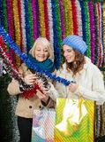 Mother And Daughter Selecting Tinsels At Store Stock Image