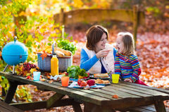 Mother and daughter set table for picnic in autumn. Happy young mother with little girl grilling meat and making sandwich and salad on a picnic table in sunny Stock Image