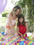 Mother And Daughter Setting Table For Birthday Party Royalty Free Stock Photography