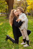 Mother with daughter seven years old in autumn Park at sunset Stock Photography