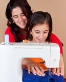 Mother and daughter sewing together. Hispanic mother  and her daughter using a sewing machine and sharing a good time together Stock Photo