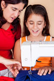 Mother and daughter sewing together. Latin  mother teaching her daughter how to use a sewing machine Royalty Free Stock Photography
