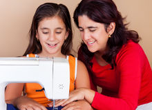 Mother and daughter sewing together. Happy hispanic mother teaching her daughter how to use a sewing machine Royalty Free Stock Images