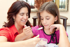 Mother and daughter sharing a dessert Stock Photo