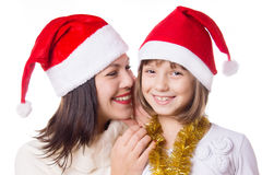 Mother and daughter sharing each other secrets on Christmas Eve. Over white Stock Photos