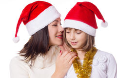 Mother and daughter sharing each other secrets on Christmas Eve. Over white Stock Photography