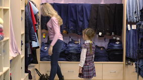 Mother and daughter shopping for clothes in a clothing store, stock video footage