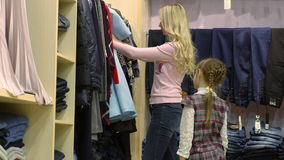 Mother and daughter shopping for clothes in a clothing store, stock footage