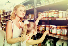 Mother with daughter shopping conserve crushed tomatoes. Glad young mother with daughter shopping conserve crushed tomatoes at a groceries Stock Images