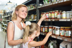 Mother with daughter shopping conserve crushed tomatoes. Glad young mother with daughter shopping conserve crushed tomatoes at a groceries Royalty Free Stock Images