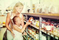Mother with daughter shopping conserve crushed tomatoes. Glad young mother with daughter shopping conserve crushed tomatoes in a groceries. Focus on child Stock Photo