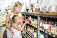 Mother with daughter shopping conserve crushed tomatoes. Glad young mother with daughter shopping conserve crushed tomatoes in a groceries. Focus on child Royalty Free Stock Photo