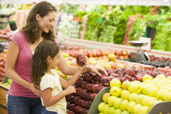 Mother and daughter shopping for fresh produce. In supermarket Royalty Free Stock Images