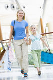 Mother and daughter shopping in mall. Carrying bags Royalty Free Stock Photos