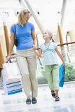 Mother and daughter shopping in mall. Carrying bags Royalty Free Stock Images