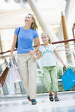 Mother and daughter shopping in mall. Mother and daughter in shopping mall carrying bags Stock Image
