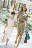 Mother and daughter shopping in mall. Carrying bags Stock Photography
