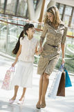 Mother and daughter shopping in mall. Carrying bags Stock Images