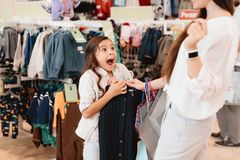 Mother and daughter in shopping mall. Girl is excited about new sweater. royalty free stock images
