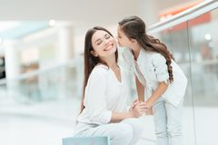 Mother and daughter in shopping mall. Girl kisses woman on cheek. royalty free stock photos