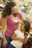 Mother and daughter shopping in produce section Stock Photos