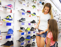 Mother and daughter shopping for shoes. Choicing sneakers Royalty Free Stock Photos