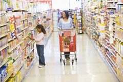 Mother and daughter shopping in supermarket. Mother and daughter shopping for groceries in supermarket Stock Photo
